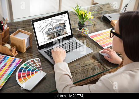 An Architect Working With Color Samples For Selection Using Laptop - Stock Photo