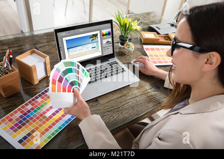 A Female Designer Using Laptop While Holding Colour Swatches In Her Hand - Stock Photo