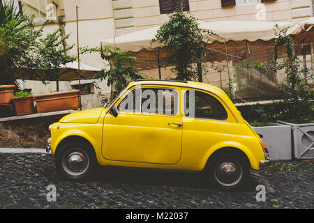A yellow small car in a roman street with stones and plants in the background - Stock Photo