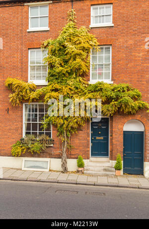 An image of a three storey house in red brick - Stock Photo