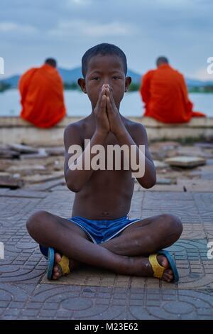 Cambodian boy posing behind monks, Kompong Chhnang, Cambodia - Stock Photo