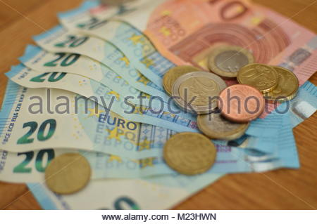 Closeup of Euro currency bank notes and coins piled on wooden table. - Stock Photo