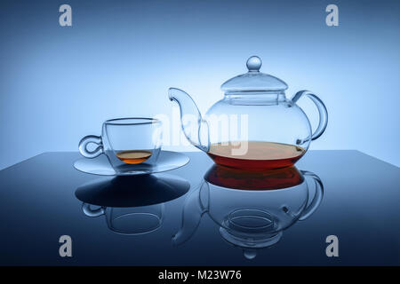 Studio image of transparent glass cup and teapot set with small amount of golden brown black tea at the bottoms - Stock Photo