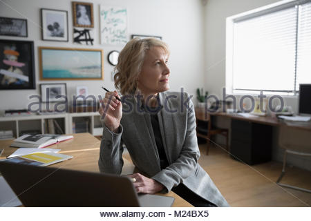 Thoughtful senior businesswoman entrepreneur working at laptop in studio office - Stock Photo