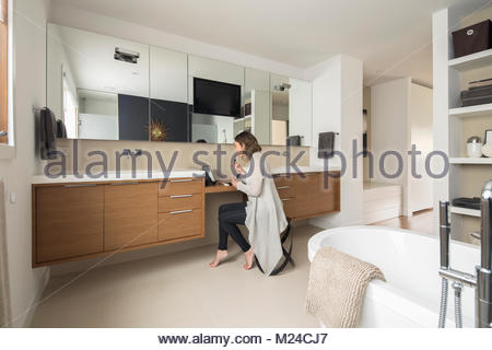 Woman applying makeup at vanity counter in home showcase bathroom - Stock Photo