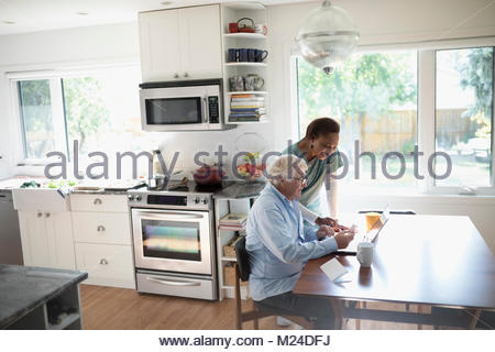 Female home nurse and senior male patient using laptop at kitchen table - Stock Photo