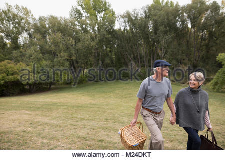 Smiling senior couple walking and holding hands, carrying picnic basket in park - Stock Photo