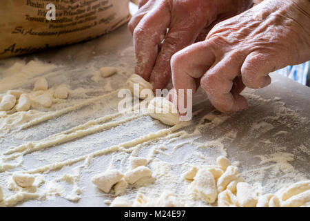 Italian woman making traditional fresh homemade pasta on a marble table - Stock Photo