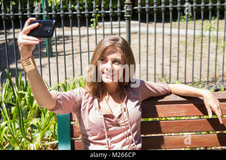 Caucasian female sitting on a bench taking a photo of herself outside - Stock Photo