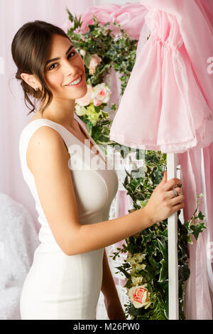 Image of young brunette in white dress on background of flowers - Stock Photo
