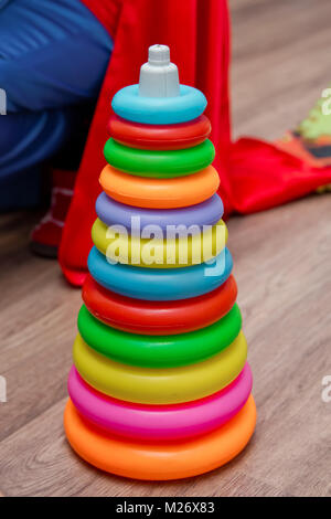 Colorful plastic rainbow toy pyramid for little kids on the blue background. Children's bright multi-colored toys. - Stock Photo