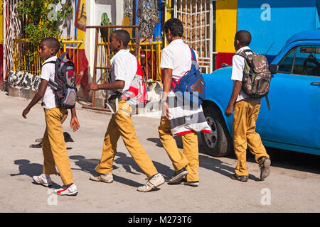Daily life in Cuba - School boys walking past colourful Cuban artwork painted on wall at Callejon De Hamel, Havana, - Stock Photo