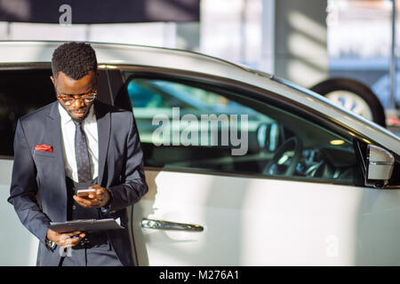 african car salesman using smart phone in showroom - Stock Photo