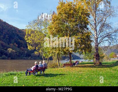 Eldery people sitting on a bench at riverside of Moselle river, Ediger, Ediger-Eller, Moselle river, Rhineland-Palatinate, - Stock Photo