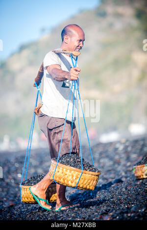 Bali, August 31, 2013: A man collects smoothen pebbles at the beach in Bali, Indonesia. Stones rounded by the sand - Stock Photo
