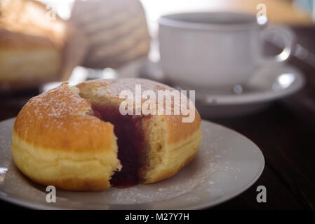 Berliner donut filled with strawberry jam. Close up - Stock Photo