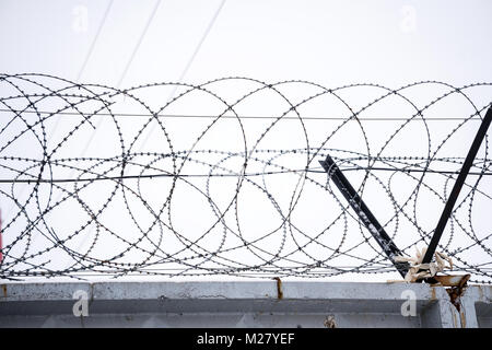 Barbed wire on concrete fence on the background of the grey sky - Stock Photo