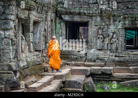 Monk in orange robe in an ancient temple in Angkor Wat, Siem Rep, Cambodia - Stock Photo