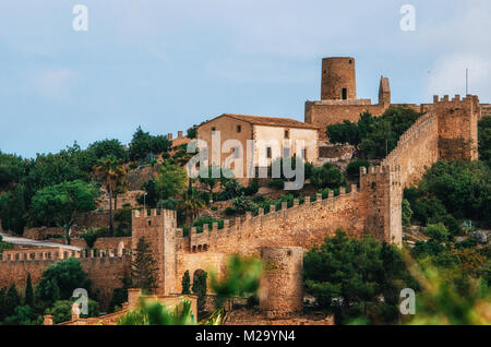 Capdepera castle on green hill in Mallorca island, Spain. Beautiful landscape with medieval architecture in Majorca - Stock Photo