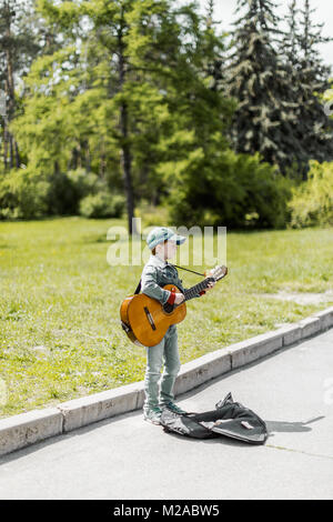 KYIV, UKRAINE May 01, 2016: Boy playing on acoustic guitar outdoors. Little street musician. Toned photo - Stock Photo