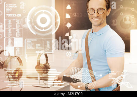 Cheerful customer holding a smartphone while choosing headphones for it - Stock Photo