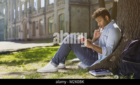 Multiracial young guy sitting under tree, reading interesting book, bookworm - Stock Photo