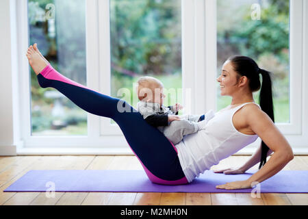 Mother exercising with her child - Stock Photo