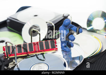 Abstract photo of the fight against content piracy. Small figure in handcuffs isolated on white background. - Stock Photo