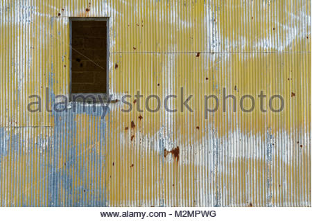 Fading paint on a corrugated metal wall that is part of an abandoned grain facility. - Stock Photo
