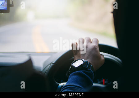 Driver hands holding steering wheel curve road, inside of a car process - Stock Photo