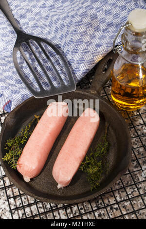 home made raw british sausages with herbs in a cast iron pan - Stock Photo