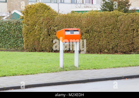 Posting a letter in the Netherlands - Orange letterbox - Stock Photo