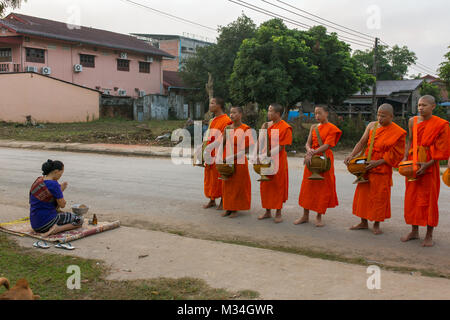 Vang Vieng, Laos - January 21, 2017: Buddhist monks collecting alms in the morning in Vang Vieng, Laos - Stock Photo