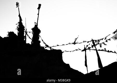 Prayer flags flying in the wind mounted on old pillar forming a silhouette - Stock Photo