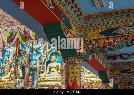 Coorg, India - October 29, 2013: Combination shot of The Buddha golden statue and columns inside Padmasambhava Vihara - Stock Photo