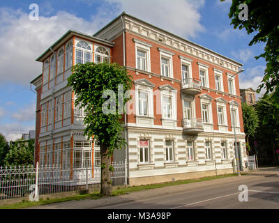 Fancy brick stone neo renaissance building on a sunny day with soft clouds in the city of Liepaja, Latvia - Stock Photo