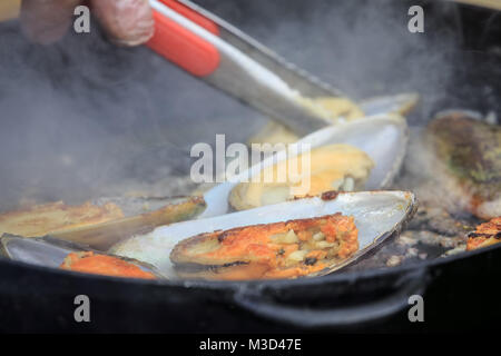 The process of cooking fried mussels in a frying pan - Stock Photo