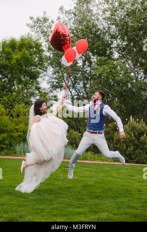 Young beautiful bride and groom make a jump on the grass at green park. Happy married couple jumping with red balloons - Stock Photo