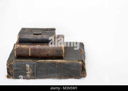 Stack of Three Antique Worn Leather Bibles on White Background - Stock Photo