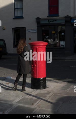 Young woman posting  a letter into a Red Royal Mail Box,Parsons Green,London,UK - Stock Photo