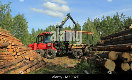 RAASEPORI, FINLAND - AUGUST 17, 2014: Unidentified machine operator stacking up wood with Komatsu 830.3 forwarder. - Stock Photo