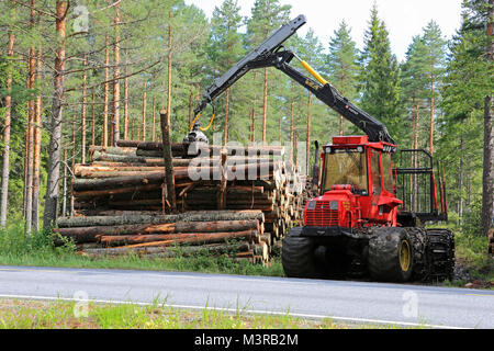 KOSKI TL, FINLAND - AUGUST 16, 2014: Sisu forestry forwarder stacking wood by road. Ca. 95% of Finnish production - Stock Photo