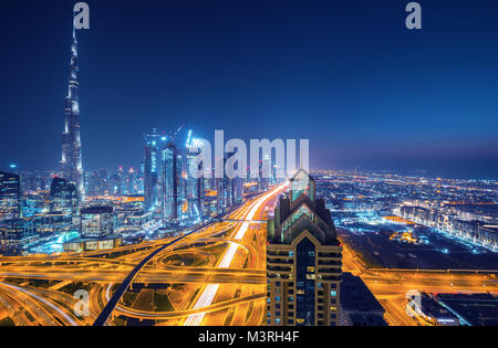 Dubai skyline at sunset with beautiful city center lights and road traffic, Dubai, United Arab Emirates - Stock Photo
