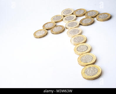 Several new twelve sided British pound coins arranged in the shape of an arrow denoting an upward trend - Stock Photo