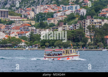 Tourist boat in Bay of Kotor, Adriatic Sea in Montenegro. Dobrota town on background - Stock Photo