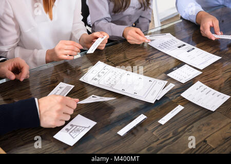 Hands Of Business People Discussing UX Mockups - Stock Photo