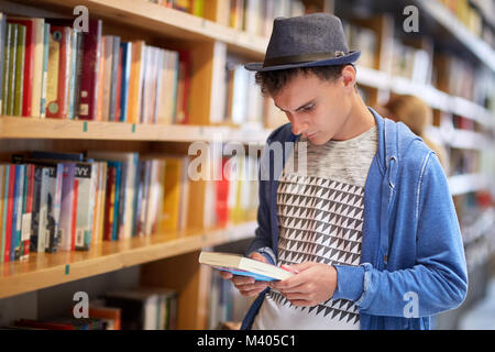 Young student choosing a book from the library - Stock Photo