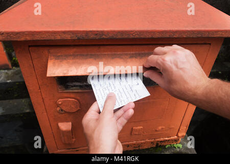 Closeup on a male hand putting a letter in a red letterbox. Concept of vintage type of communication. - Stock Photo