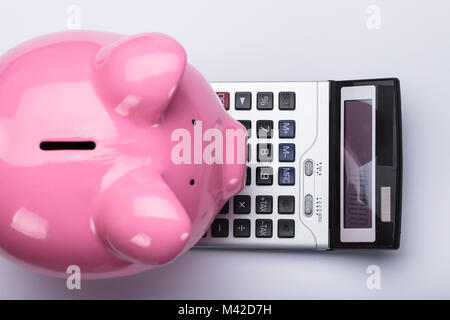 Elevated View Of Pink Piggy Bank And Calculator On White Background - Stock Photo