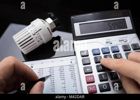 Close-up Of A Human Hand Calculating Financial Report Near Thermostat Radiator - Stock Photo
